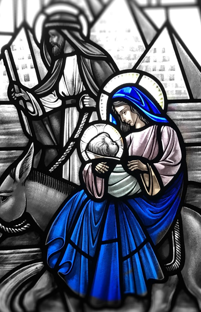 An image of a stained glass window of the Flight into Egypt from the Nave of Saint David of Wales Church. Denton Texas